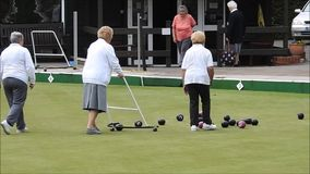 Retraités d'oap de membres expérimentés jouant des sports actifs de bowling green de cuvettes dehors banque de vidéos