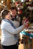 Retraités féminins achetant des décorations de Noël à la foire Image stock
