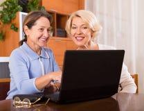 Retraités féminins avec l'ordinateur portable d'intérieur Photo stock