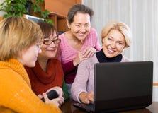 Retraités féminins avec l'ordinateur portable d'intérieur Photos stock