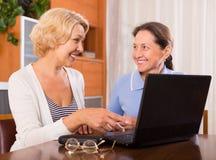 Retraités féminins avec l'ordinateur portable d'intérieur Images stock