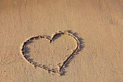 Retrait de coeur dans le sable sur la plage Photographie stock