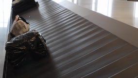 Retrait des bagages dans l'aéroport international Valises passant la bande de conveyeur banque de vidéos