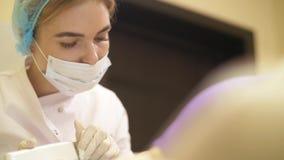 Retrait haut étroit de laser de procédure des points noirs de la peau d'une jeune femme dans une clinique cosmétique clips vidéos