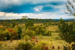 Retranchez-vous sur le ciel avec des nuages et des champs avec les buissons jaunes et rouges images libres de droits