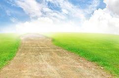 Retrate a estrada do campo verde e do céu azul Fotografia de Stock Royalty Free