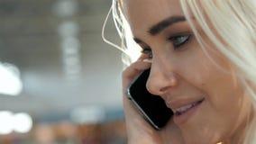 Retrato à moda de um louro novo bonito que fala no telefone no fundo da rua que sorri e que levanta em Imagem de Stock