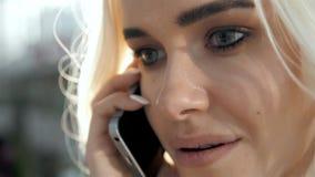 Retrato à moda de um louro novo bonito que fala no telefone no fundo da rua que sorri e que levanta em Imagens de Stock