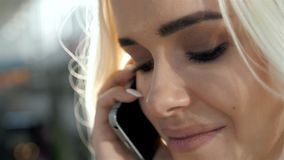 Retrato à moda de um louro novo bonito que fala no telefone no fundo da rua que sorri e que levanta em Foto de Stock Royalty Free