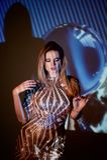 Retrato abstracto de una muchacha hermosa teniendo en cuenta el proyector La atmósfera del disco 80 x Lentejuelas de oro A Foto de archivo