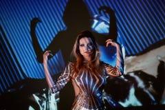 Retrato abstracto de una muchacha hermosa teniendo en cuenta el proyector La atmósfera del disco 80 x Lentejuelas de oro A Foto de archivo libre de regalías