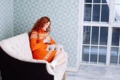 Retrato acogedor de la mujer en suéter caliente en la cama con la taza de t Imagen de archivo