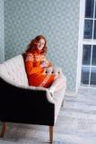Retrato acogedor de la mujer en suéter caliente en la cama con la taza de t Fotos de archivo libres de regalías