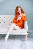 Retrato acogedor de la mujer en suéter caliente en la cama con la taza de t Foto de archivo