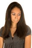Retrato adolescente hispánico lindo de la muchacha que mira abajo con los labios fruncidos Foto de archivo libre de regalías
