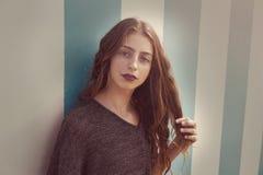 Retrato adolescente moreno de la muchacha en pared de las rayas azules Fotografía de archivo libre de regalías