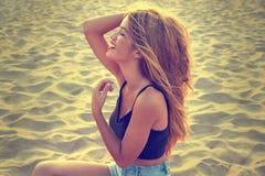 Retrato adolescente rubio de la muchacha en la arena de la playa Imagenes de archivo