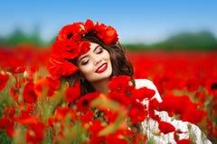 Retrato adolescente sonriente feliz hermoso de la muchacha con las flores rojas en h Fotos de archivo libres de regalías