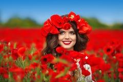 Retrato adolescente sonriente feliz hermoso de la muchacha con las flores rojas en h Fotos de archivo