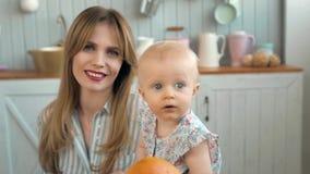 Retrato adorable del pequeño niño, familia cariñosa feliz mime a jugar con su bebé en la cocina, mamá sonriente con blanco almacen de video