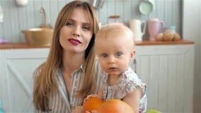 Retrato adorable del pequeño niño, familia cariñosa feliz mime a jugar con su bebé en la cocina, mamá sonriente con blanco almacen de metraje de vídeo