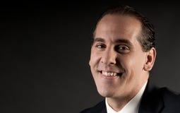 Retrato adulto do close up do homem de negócios que sorri na obscuridade imagem de stock