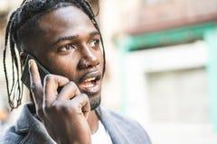 Retrato afro-americano atrativo do indiv?duo que fala no telefone celular na rua imagens de stock royalty free