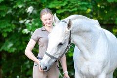 Retrato agraciado del caballo blanco con su adolescente del dueño-blondy Foto de archivo