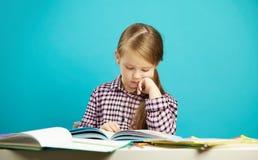 Retrato aislado de la muchacha en fondo azul, sentándose en el escritorio, leyendo el libro cuidadosamente con su mano a la barbi Foto de archivo libre de regalías