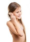 Retrato aislado de la muchacha sonriente que escucha la concha marina Foto de archivo