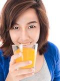 Retrato aislado de la mujer feliz joven que bebe el SMI del zumo de naranja Fotos de archivo