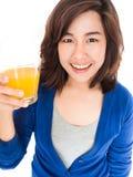 Retrato aislado de la mujer feliz joven que bebe el SMI del zumo de naranja Foto de archivo libre de regalías