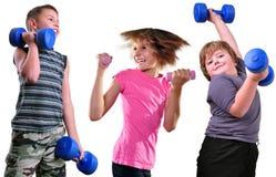 Retrato aislado de los niños que ejercitan con pesas de gimnasia Fotos de archivo
