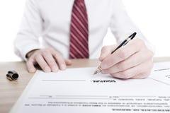 Retrato aislado de un hombre de negocios que firma un contrato imagen de archivo