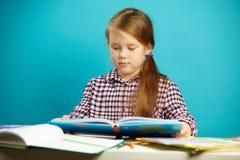 Retrato aislado del alumno en el escritorio que sostiene un libro en sus manos y que lee entusiasta Chica joven adentro primero Imagen de archivo libre de regalías