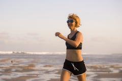 Retrato aislado del fondo de la mujer feliz y atractiva joven del ajuste que corre en la playa en entrenamiento al aire libre que imagenes de archivo