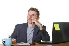 Retrato aislado del hombre de negocios acertado y atractivo joven que trabaja en el escritorio del ordenador de oficina satisfech imagenes de archivo