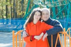 Retrato al aire libre de abrazar la hija adulta y a su padre mayor en el fondo del parque de atracciones de la montaña rusa imagen de archivo