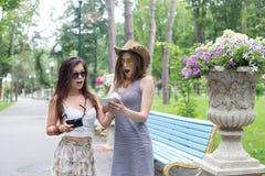Retrato al aire libre de dos amigos que miran las fotos con un smartphon Fotografía de archivo libre de regalías