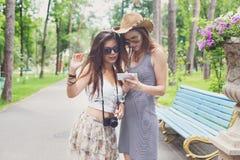 Retrato al aire libre de dos amigos que miran las fotos con un smartphone Imagenes de archivo