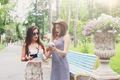 Retrato al aire libre de dos amigos que miran las fotos con un smartphone Fotografía de archivo