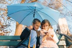 Retrato al aire libre de dos niños sonrientes de muchacho y de muchacha, sentándose debajo de un paraguas en banco en el parque,  imagenes de archivo