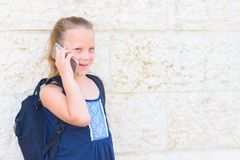 Retrato al aire libre de hablar de 8-9 a?os de la muchacha feliz en el tel?fono imagenes de archivo