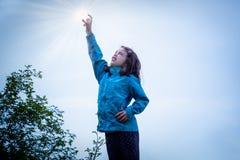 Retrato al aire libre de la chica joven en la chaqueta azul que alcanza su brazo en el aire para coger el sol fotos de archivo libres de regalías