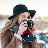 Retrato al aire libre de la forma de vida del invierno de la mujer bastante rubia con la cámara retra Foto de archivo libre de regalías