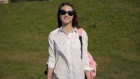 Retrato al aire libre de la moda de la muchacha atractiva joven El skater femenino elegante hermoso lleva las gafas de sol en par almacen de video