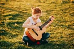 Retrato al aire libre de la muchacha de 9 años adorable del niño que toca la guitarra al aire libre Imagenes de archivo
