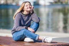 Retrato al aire libre de la muchacha adolescente sonriente feliz joven en la parte posterior del infante de marina Imagen de archivo