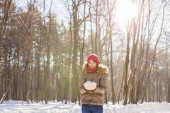 Retrato al aire libre de la muchacha de la Navidad Nieve que sopla de la mujer del invierno en un parque Fotos de archivo libres de regalías