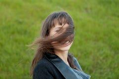 Retrato al aire libre de la muchacha hermosa que ríe mientras que el viento se mueve Foto de archivo